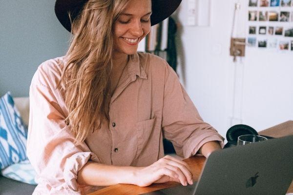 femme qui sourit en faisant des recherches sur internet